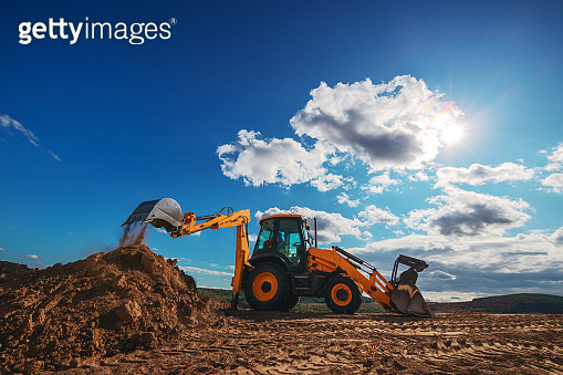 Wheel loader excavator with field background during earthmoving work, construction building