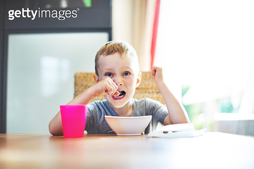 Little boy eating cereal for breakfast