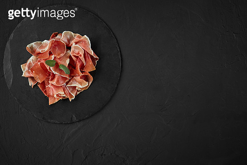 Gourmet, manually sliced jamon with herbs on black stone slate board against a dark grey background. Close-up shot. Top view. Copy space