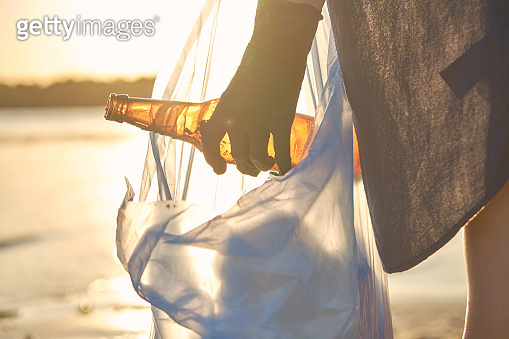Young volunteer in black gloves is walking with garbage bag along a dirty beach of the river and cleaning up trash. People and ecology. Close-up