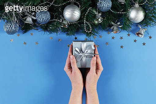 Christmas background with gift in hand and sparkling lights, decorations on fir branches on blue canvas background.