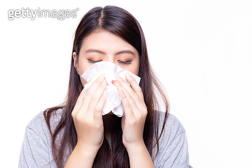 Beautiful asian woman has a cold or flu. She feel sick and dizzy. Pretty girl blowing nose by using tissue paper. She has nasal congestion or stuffed nose and running nose. She get sinusitis disease