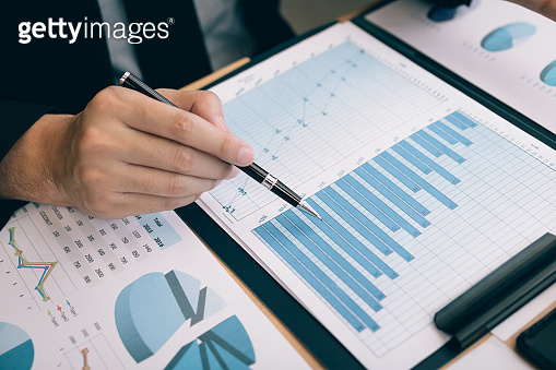 Businessmen are using the pen pointing to the cost and expense graph of the company.