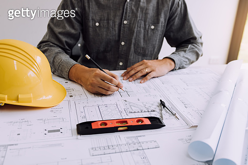 Hand of young engineering man drawing on blueprint at table in office room.
