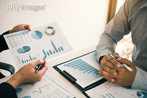 Two business partnership coworkers analysis strategy and gesturing with discussing a financial planning graph and company budget during a budget meeting in office room.