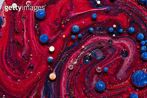 blue and red paint drops on red background