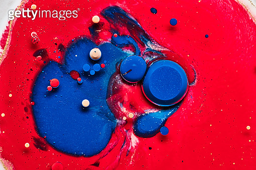 blue and yellow paint drops on red background
