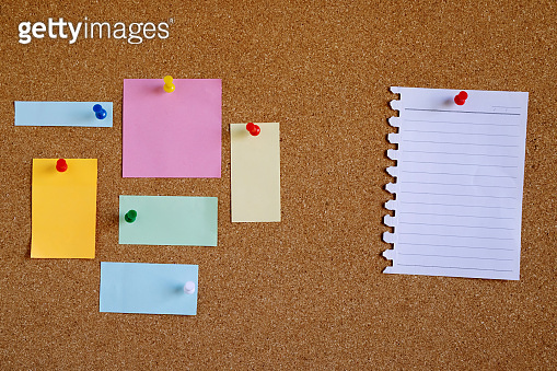 Piece paper of blank white note pad reminder and collection of colorful variety post. stick colorful push pin to a cork bulletin board. empty space for text write a note.