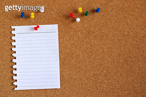 Piece paper of blank white note pad variety post stick push pin red to a cork board. empty space for text write a note.