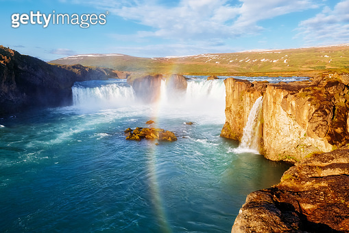 Nice views of the bright sunlit powerful Godafoss cascade. Location Skjalfandafljot river, Iceland, Europe.