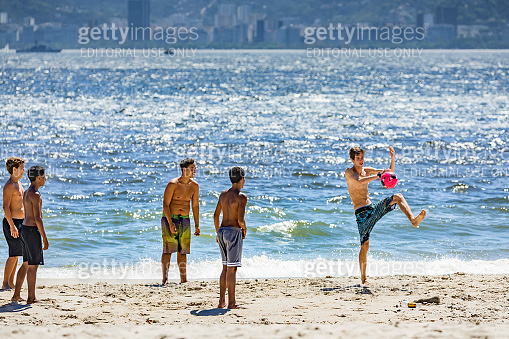Brazilian young men playing soccer on Ipanema Beach at sunset in Rio de Janeiro Brazil