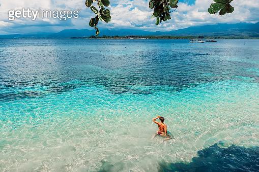 Young bikini woman relax in blue ocean on tropical island