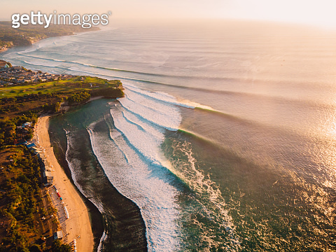 Aerial view of waves at warm sunset and beach. Ideal ocean waves for surfing
