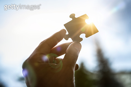 The man holds in his hand a jigsaw puzzle.