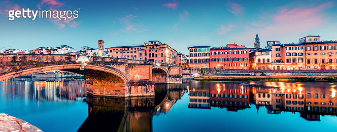 Picturesque medieval arched St Trinity bridge (Ponte Santa Trinita) over Arno river. Colorful spring sunset in Florence, Italy, Europe. Traveling concept background.