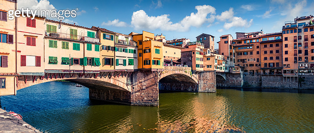 Picturesque medieval arched river bridge with Roman origins - Ponte Vecchio. Colorful spring morning view of the Arno river in Florence, Italy, Europe. Traveling concept background.