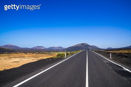 Spain, Lanzarote, Black asphalt road alongside pretty volcanic nature landscapes and volcanoes