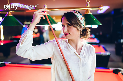 Young woman with pool cue