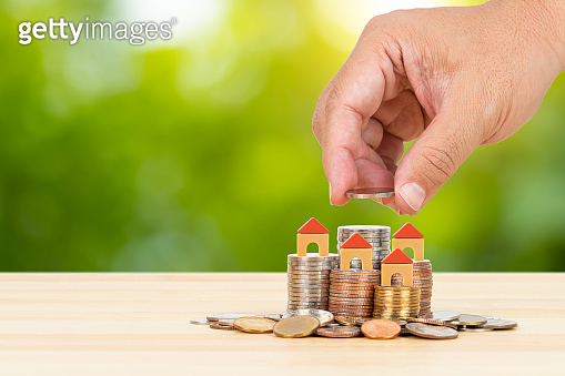 Model house on coin stack and hand placing money, on wooden desk over green tree background, mortgage concept