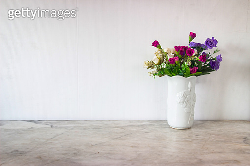 Isolate  art white basket and colorful flowers place on grey marble surface table and white and clear Concrete wall. Abstract background  and nobody template with relaxation feeiling clean and clear.