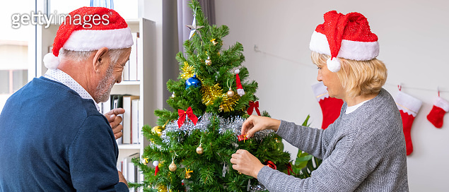 Caucasian senior couple elderly man and woman decorating Christmas tree together for the festival