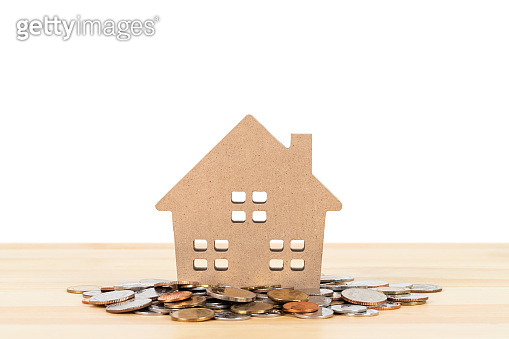 Model house over coin pile on wooden desk on white background, mortgage concept