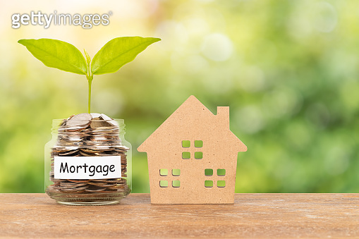 Model house and money coin jar on green tree background mortgage saving concept