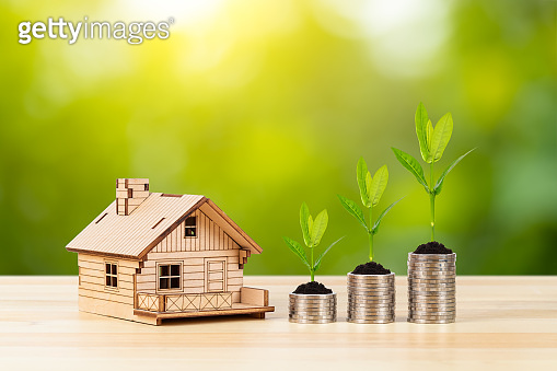 Coin stack and model house with growing leaves on wooden desk on green tree background, mortgage concept