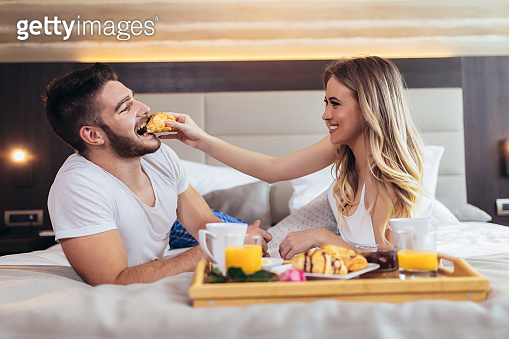 Young happy couple having breakfast in luxury hotel room.