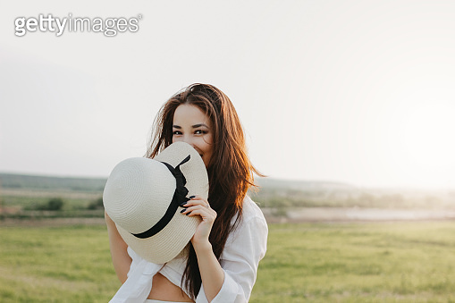 Portrait of charming carefree long hair asian girl in white clothes and straw hat enjoys life in the nature field at sunset. Sensitivity to nature concept