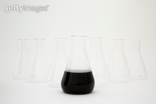 Scientific laboratory glass erlenmeyer flask filled with black liquid with glassware equipment on white background.