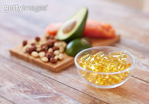 close up of omega 3 capsules and food on table