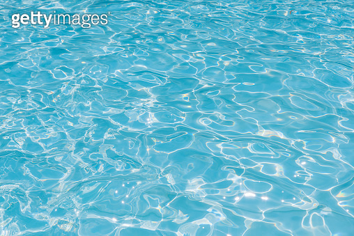 Blue water in pool for background and abstract, Ripple wave with sun reflection in swimming pool, Clean and bright purified water for healthy swimming