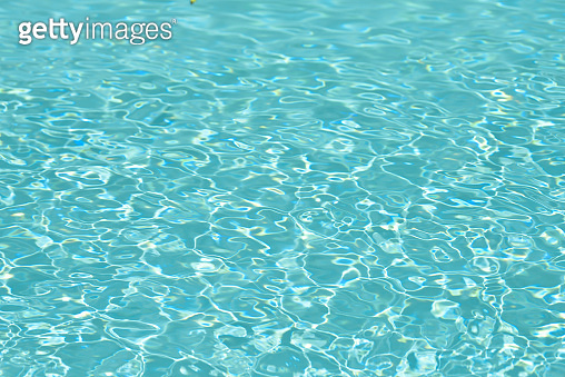 Abstract of blue water surface in swimming pool, Ripple wave in pool with sun reflections
