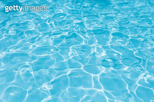 Abstract of blue water surface in swimming pool, Ripple wave in pool with sun reflection