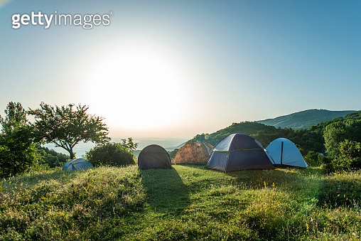 Many tents in the mountain. Sunshine morning in the forest.