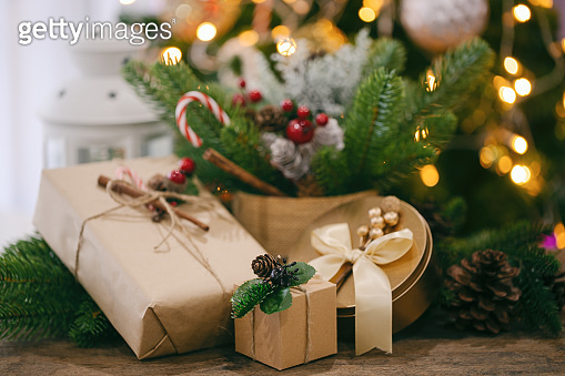 Christmas decoration sweet background with gift box, pine leaves and pine cones, white lantern and candy cane on wood table with copy space. Bokeh Christmas tree wallpaper for xmas celebration