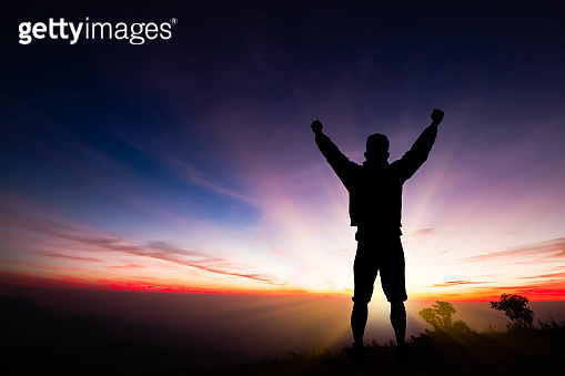 Silhouette of young man standing on top of mountain with fists raised up on sunrise background, successful, achievement and winning concept