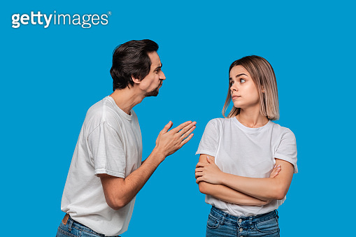 Brunet bearded man with mustaches in white t-shirt and blue jeans asking his girlfriend for forgiveness isolated over blue background. Concept of guilt.