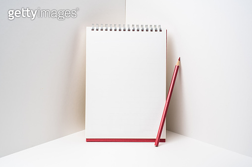 red spiral notebook with white page on 3D space