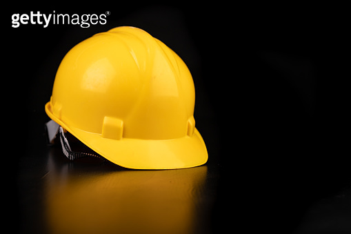 Yellow helmet on a dark workbench. Protection accessories for construction workers. Dark background.