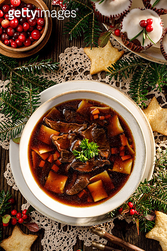 Christmas mushroom soup, a traditional vegetarian  mushroom soup made with dried forest mushrooms in a ceramik plate on a festive table,