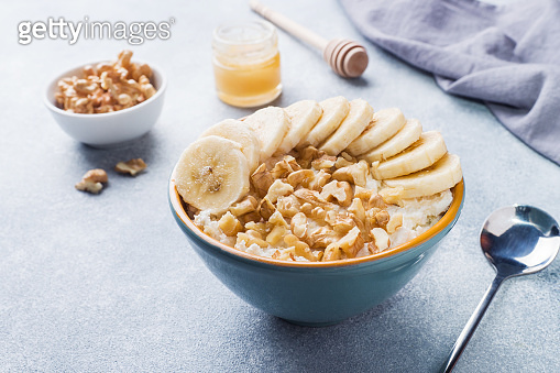 Healthy breakfast. Cottage cheese with banana and walnuts on grey background.