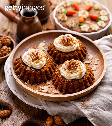 Carrot-nut muffins with mascarpone cream decorated with walnuts, pine nuts and cinnamon on a wooden plate.