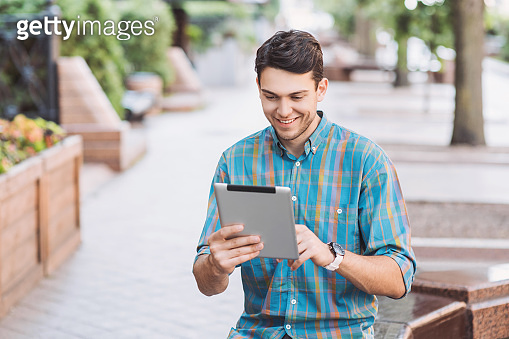 Cheerful young man using digital tablet in a city