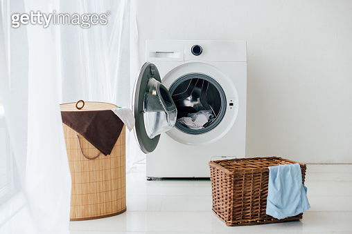 opened washer and brown baskets in laundry room
