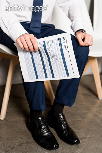 cropped view of man holding resume while sitting on chair