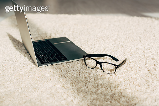 modern laptop near glasses on carpet in room with sunshine