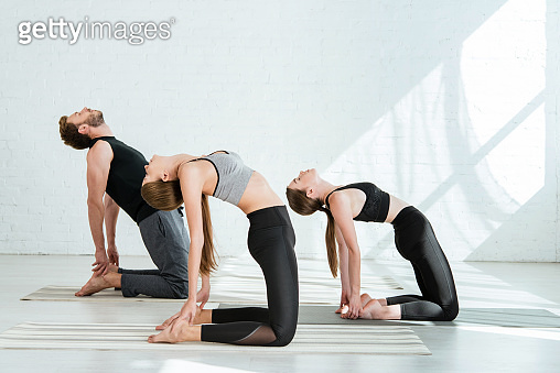 two young women and man practicing yoga in camel pose