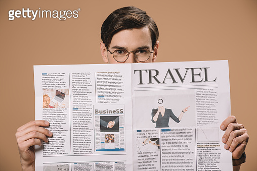 man in glasses holding travel newspaper isolated on beige
